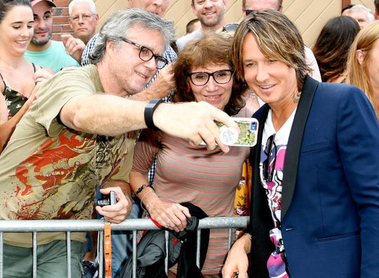 Keith Urban takes a photo with fans at the 13th Annual ACM Honors at the Ryman Auditorium on Wednesday.