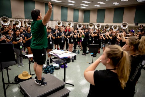 Assistant band director Joseph Bigler, center, conducts band members as they play The National Anthem during marching band practice at Palmetto Ridge High School on Thursday, August 15, 2019.