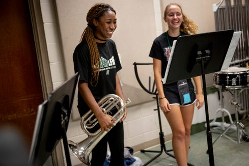 "Ahsiya Cumberbatch, left, and Paige Brokopp, right, laugh after Ahsiya finishes reciting all of the lyrics to a verse from Katy Perry's ""Dark Horse"" during marching band practice at Palmetto Ridge High School on Thursday, August 15, 2019."