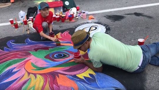 Jaden Gallus, 11, and his dad Eric Gallus work on their chalk chicken during the Naples Chalk Art festival on Fifth Avenue South on March 9.
