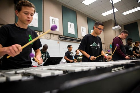From left to right, Jacob Hovey, Christian Mormion, and Ray Patterson play the marimbas during marching band practice at Palmetto Ridge High School on Thursday, August 15, 2019.