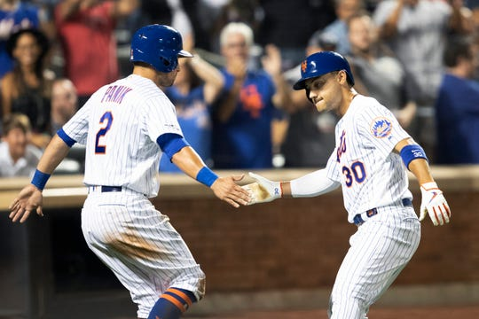 New York Mets' Michael Conforto (30) celebrates hitting a home run with Joe Panik (2) during the sixth inning of a baseball game against the Cleveland Indians, Tuesday, Aug. 20, 2019, in New York.