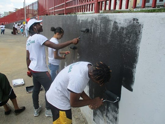 Teens painting a mural at John F. Kennedy High School they created as part of a summer jobs program.