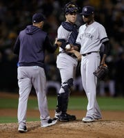 New York Yankees pitcher Domingo German, right, hands the ball to manager Aaron Boone during the sixth inning of the team's baseball game against the Oakland Athletics on Tuesday, Aug. 20, 2019, in Oakland, Calif. (AP Photo/Ben Margot)
