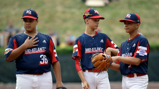 Elizabeth, New Jersey's Derek Escobar (36), Sal Garcia and J.R. Rosado (9) talk on the field against River Ridge, Louisiana during the first inning of a baseball game at the Little League World Series tournament in South Williamsport, Pa., Wednesday, Aug. 21, 2019.
