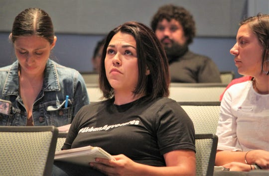 Krysten Aguilar examines a slide presentation during discussion of a ban on glyphosate-based herbicides on city property during the Las Cruces City Council meeting on Monday, Aug. 19, 2019.