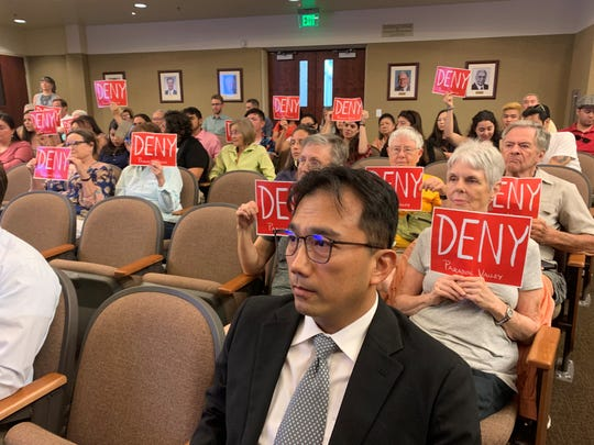 Paul Lin, president of GLC Enterprises LLC, is surrounded by opponents of the Paradise Valley project he wants to develop near Joshua Tree National Park  on Aug. 21, 2019.
