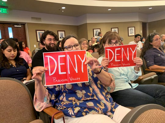 Two opponents of the proposed Paradise Valley development hold signs as a Riverside County Planning Commission member said he would vote in favor of continuing the consultation off-calendar instead of denying the development on Aug, 21, 2019.
