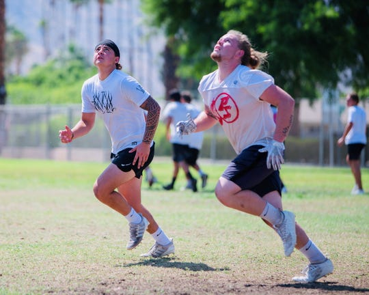 Casey Libretti (left) and Justin Murray chase down a punt during summer football practice at Palm Springs High School.