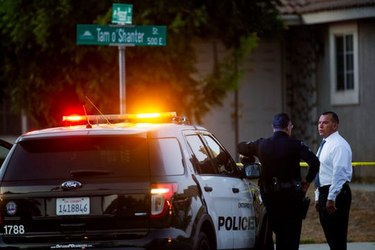Ontario Police stand outside the scene where two children, an infant and a teenager, were found dead with their mother, who was unresponsive, at a home, Tuesday, Aug. 20, 2019, in Ontario, Calif. (Terry Pierson/The Orange County Register via AP)