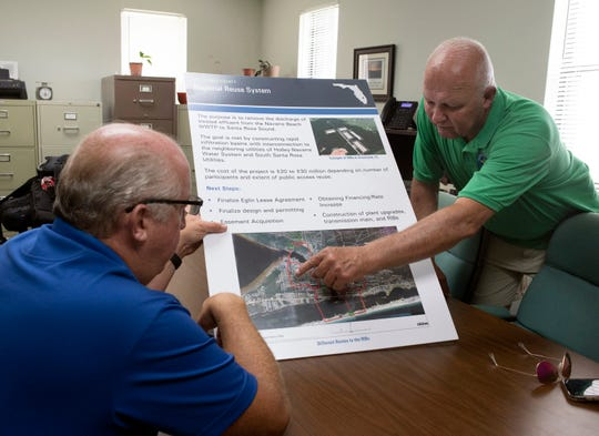 Santa Rosa County Commissioner Dave Piech and Terry Wallace, utilities director for Santa Rosa County, review plans to pump the utility's treated water to a site on the Eglin Air Force Base during a meeting Wednesday.