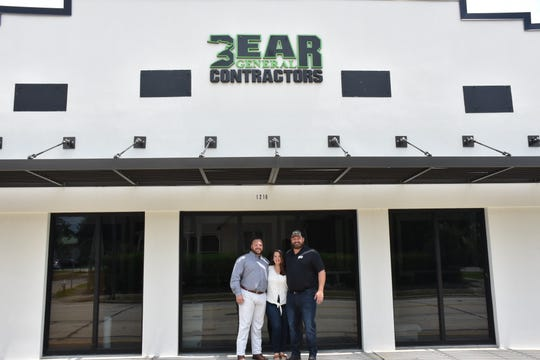 Josh Sitton, wife Kristen and co-business partner Chris Jaubert outside the new company office of Bear General Contractors on North Palafox Street.