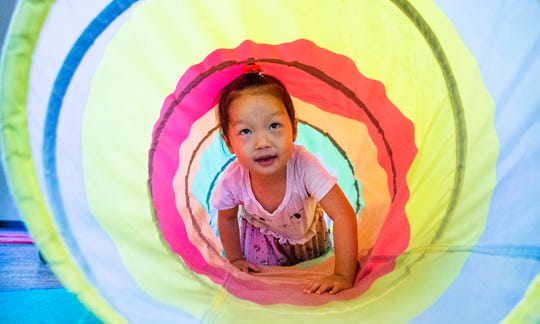 Jolin Zhang, 2, crawls through a tunnel during play time at the Magical Journey Learning Center in Ahwatukee, Tuesday, August 13, 2019.