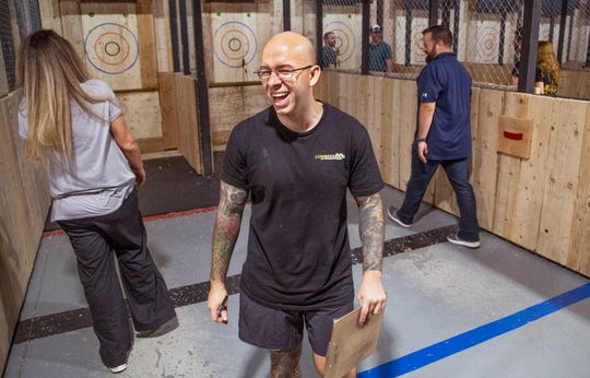 Ax coach Harvey Munera has fun supervising ax-throwing competitions at Lumberjaxes in Tempe, Wednesday, August 14, 2019.