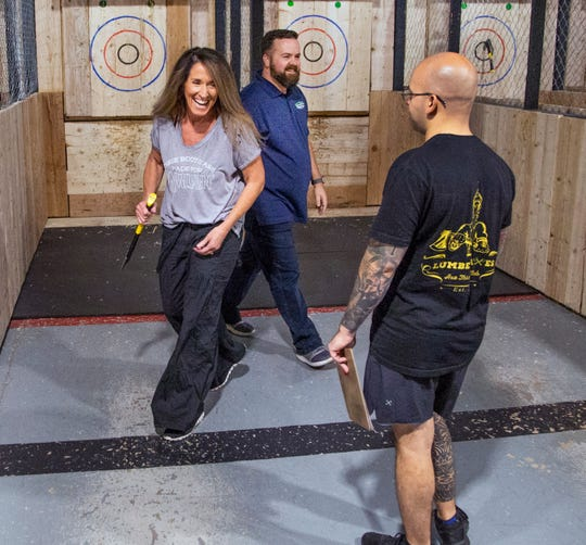 Axe coach Harvey Munera, middle, supervises Donna Rivituso, left, and Ryan Delviken in axe-throwing competition at LumberJaxes in Tempe, Wednesday, August 14, 2019.
