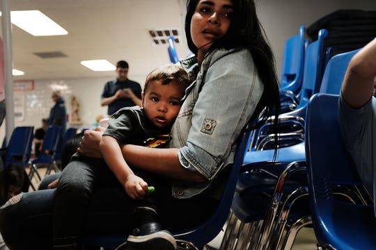 Una mujer sostiene en sus brazos a un niño migrante detenido en una estación de Texas.