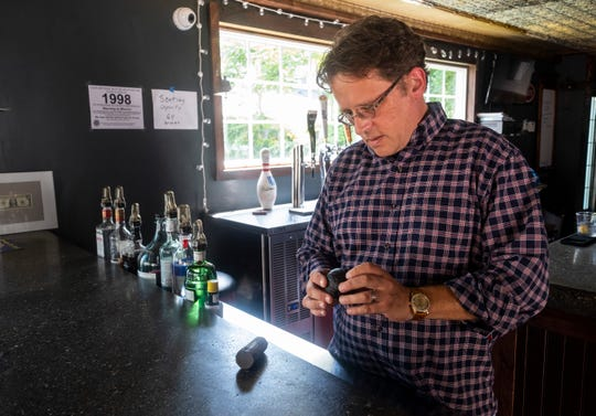 Pete Pashley, owner of Newport Pub in Marine City, examines a cannonball expected to be from between 1812 and 1814 that was found during the renovation of the bar.