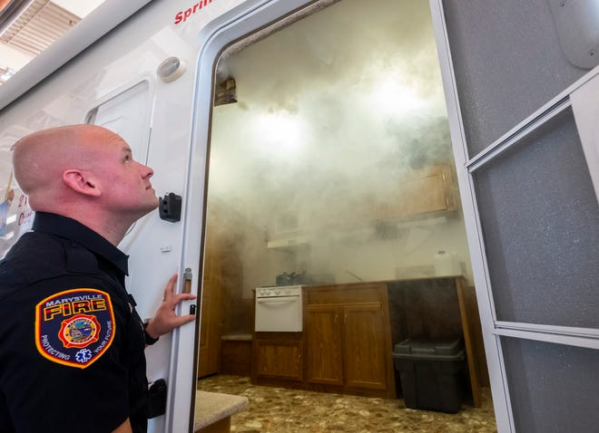 Marysville Fire Public Education Coordinator Matthew Reeves watches the department's safety trailer fill with smoke during a simulation Wednesday, Aug. 21, 2019, at the Marysville Public Safety building. The trailer is one of the demonstrations that will be held during the department's open house this Sunday.