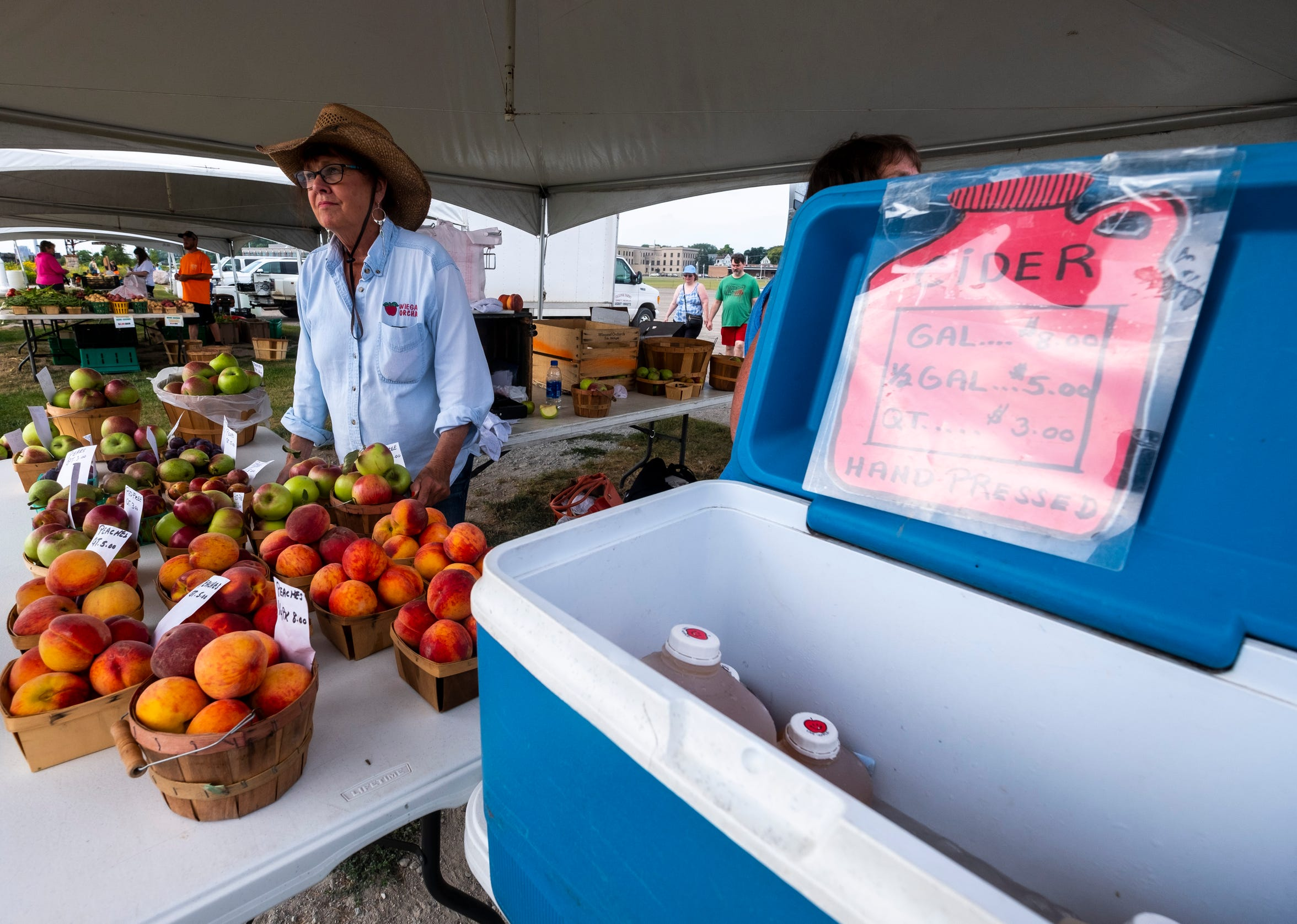 Joann Tanton works behind the tables of the Wiegand Orchard stand at the Vantage Point Farmer's Market Tuesday, Aug. 20, 2019, at Desmond Landing.