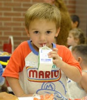 Pre-kindergartner Wyatt Harris sips milk during lunch.