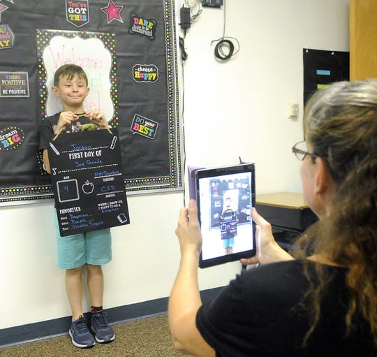 Paraprofessional Taara Williams takes photos of third graders in Michelle Trousdale's class on the first day of school.
