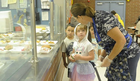 Janet Russell helps kindergartner Adalyn Gillespie make a lunch selection.