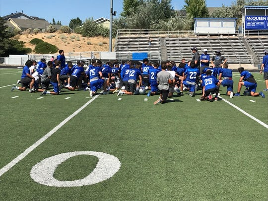 McQueen players listen to the coaches after practice on Aug. 17