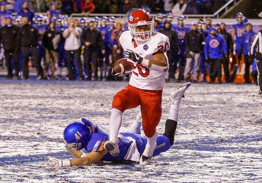 Fresno State running back Ronnie Rivers runs past the Boise State defense for the winning touchdown in overtime in last season's Mountain West championship game. Both teams are the preseason favorites to win their respective divisions.