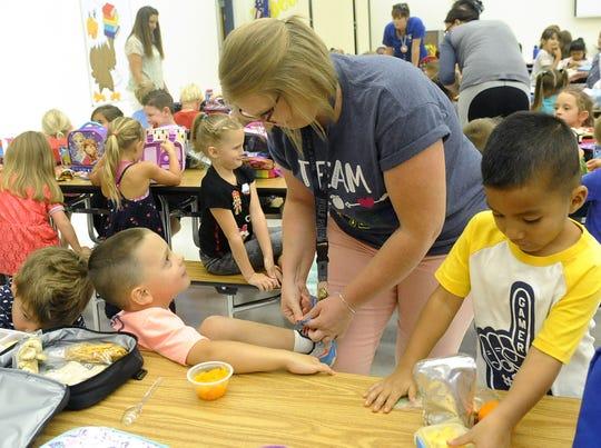 Kindergarten teacher Krystle Turner ties a student's shoe.