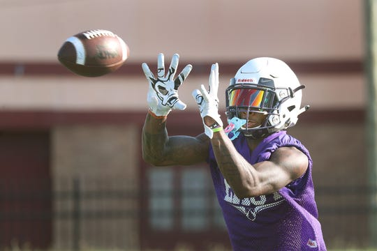 East's Seven McGee catching balls during defensive back drills.