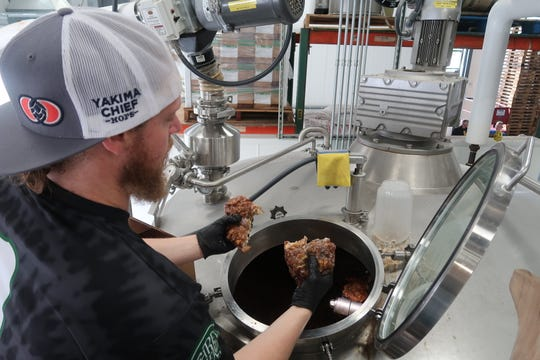 Three Heads brewer Derek Armstrong adds Donuts Delite apple fritters directly to the mash during a brew day Wednesday.