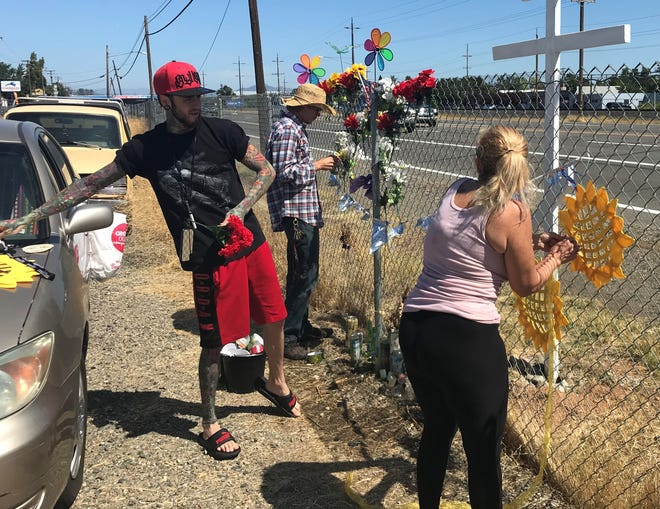 Skyler Parker, left, Garrett  Kenney and Cami Hernandez work on a memorial set up along Highway 273 in south Redding for Hernandez's son, Brandon Englund, who was killed there in June in a motorcycle crash.