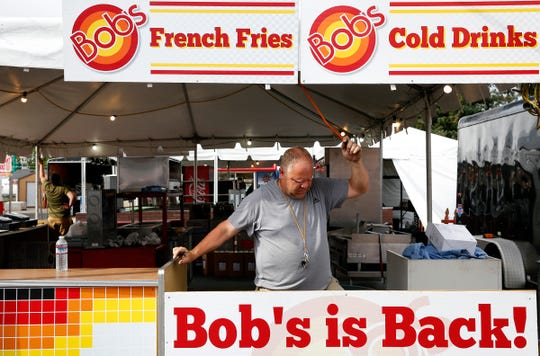 Larry Dankenbring of Bob's Burgers runs an extension cord at one of his eight booths at the Oregon State Fairgrounds in Salem, Oregon, on Tuesday, Aug. 20, 2019.