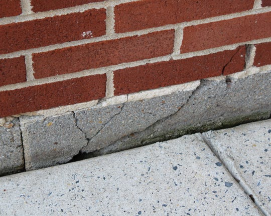 Cracking and sidewalk settling have led to visible damage to the exterior of the Sussex Tech high school building.