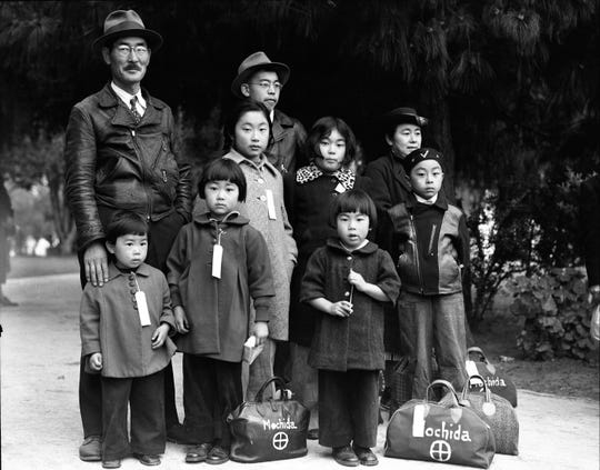 One image of the traveling exhibit shows the Mochida family, wearing identification tags, as they wait for a bus. The family was forced to leave their nursery and greenhouse operation in Eden, California in May 1942.