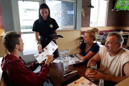 Server Zoe Harris takes the lunch order of the Lazcano family, as they take a break from spending the morning moving Alex, left, a sophomore, into Florida State University for the semester Monday, August 19, 2019.