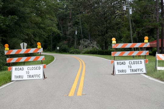 """""""Road closed to thru traffic"""" signs posted at the intersection of Hutchinson Ferry Road and Glory Road leading to the bridge in Gadsden County, which collapsed and sent two cars airborne Wednesday, Aug. 21, 2019."""