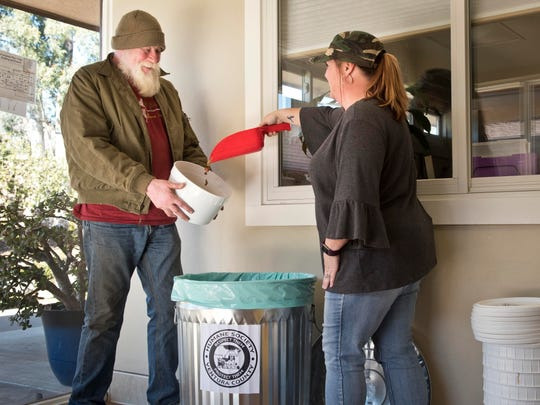 Humane Society of Ventura County Kennel Manager Angela Hanline scoops out dry dog food for Jon Christopher recently as the society's shelter in Ojai. The society is expanding its pet food program across Ventura County.