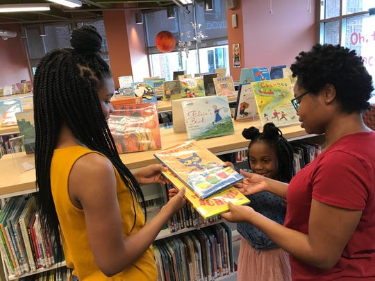(from left) Zaria Hathorn and Hailey and Victoria Willard at the Dover Library, deciding on what books the girls will read on their Facebook Live program.