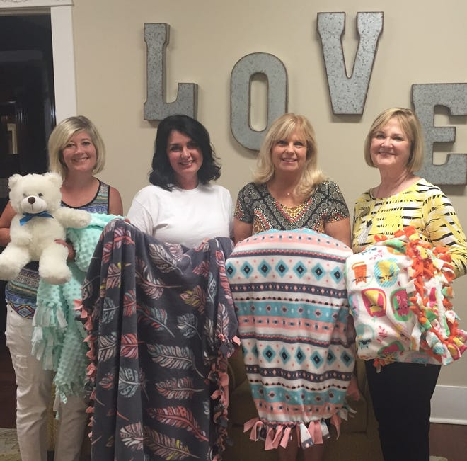 Senior-Junior Forum members recently teamed with Special Olympics Athletes to help make fleece blankets for Patsy's House Children's Advocacy Center. Delivering blankets (from left to right) are Shelly Hutchins, Denise Roberts, Exective Director of Patsy's House, Ladell Schmalzried and Annette Barfield.