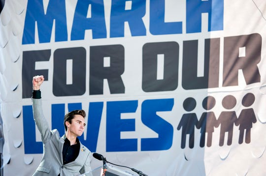 FILE - In this March 24, 2018, file photo, David Hogg, a survivor of the mass shooting at Marjory Stoneman Douglas High School in Parkland, Fla., raises his fist after speaking during the March for Our Lives rally in support of gun control in Washington. (AP Photo/Andrew Harnik, File)
