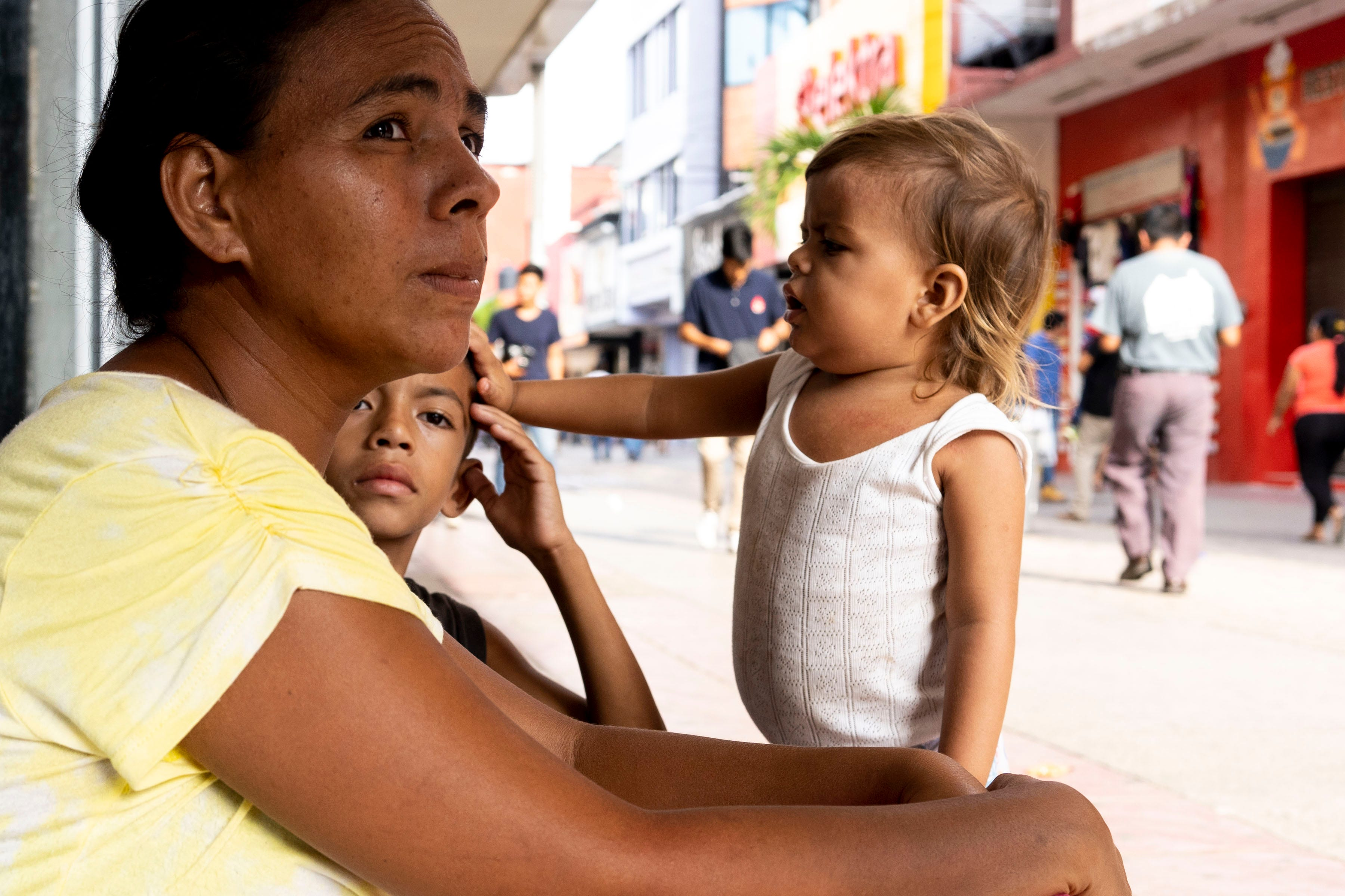TAPACHULA, México – Waldina Bonilla Rodríguez, de Honduras, trata de no perder de vista a su hijo de 8 años, Oscar, mientras el pequeño camina entre la muchedumbre descalzo y pidiendo dinero. Rodríguez extiende una taza de plástico mientras su hija de dos años, Delin Nicol, tira de su camiseta sin mangas. La pequeña llora pidiendo atención, su cabello rubio lleno de nudos.