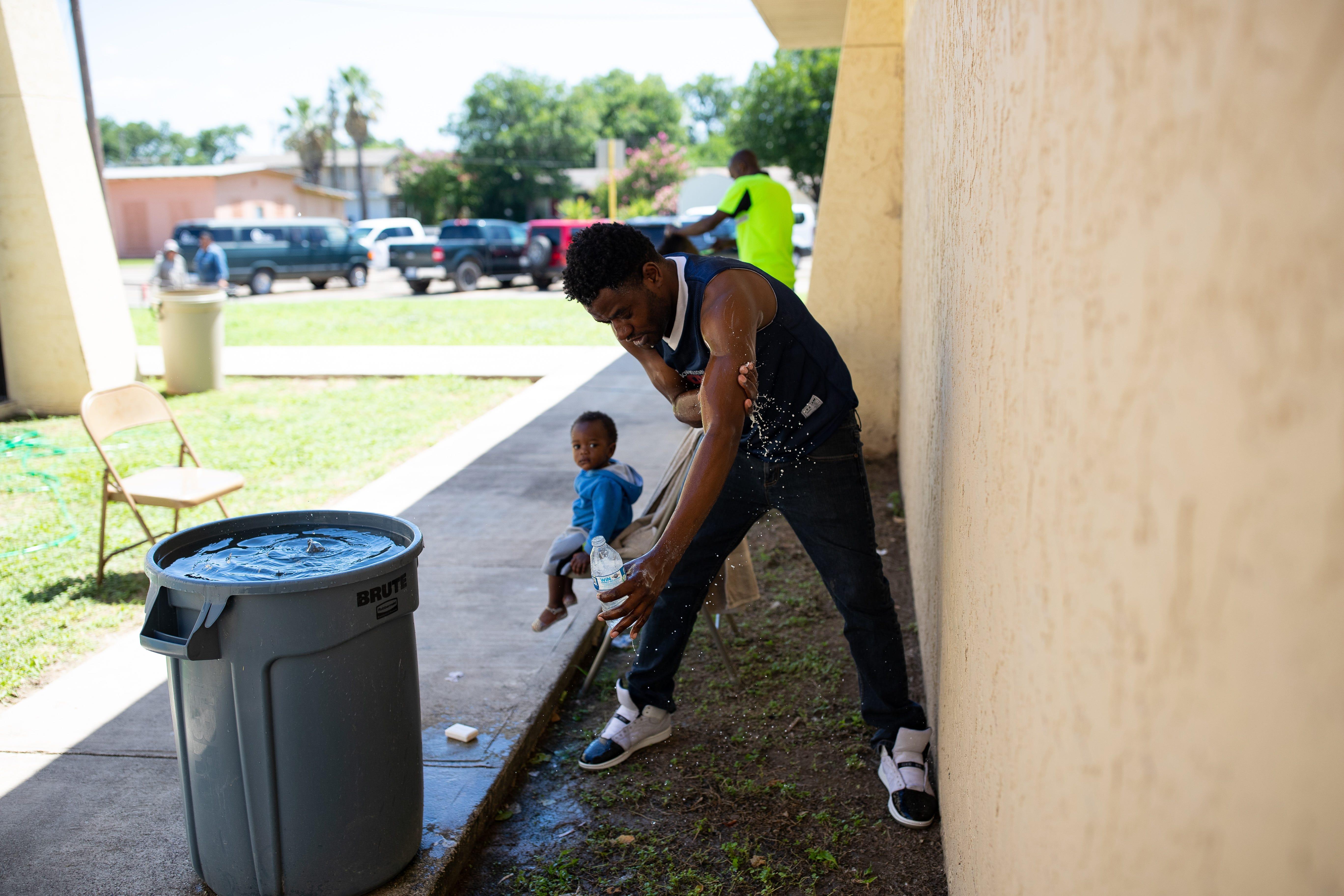 DEL RIO, Texas – Un migrante se baña usando el agua sucia que descarga una unidad de aire acondicionado rota en el Centro de la Coalición Humanitaria de la Frontera Val Verde el 25 de junio del 2019, mientras esperaba por un autobús que lo transportara al Centro de Recursos para Inmigrantes de San Antonio.