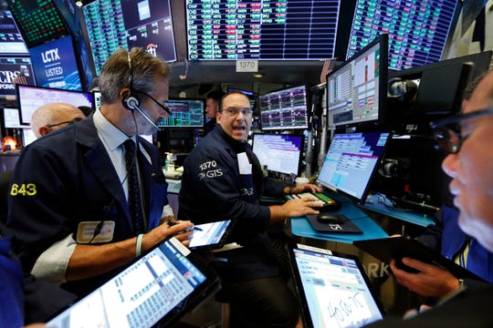 Specialist Anthony Matesic, center, works with traders at his post on the floor of the New York Stock Exchange, Wednesday, Aug. 21, 2019.