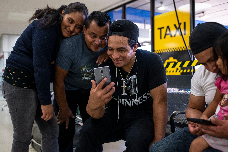 NEWARK, N.J. –  Leydi González, 29, a la izquierda, y Jaime Escalante Galvez, 35, ven videos con su hermano, Abner González, 22, en el Aeropuerto Internacional Newark Liberty.