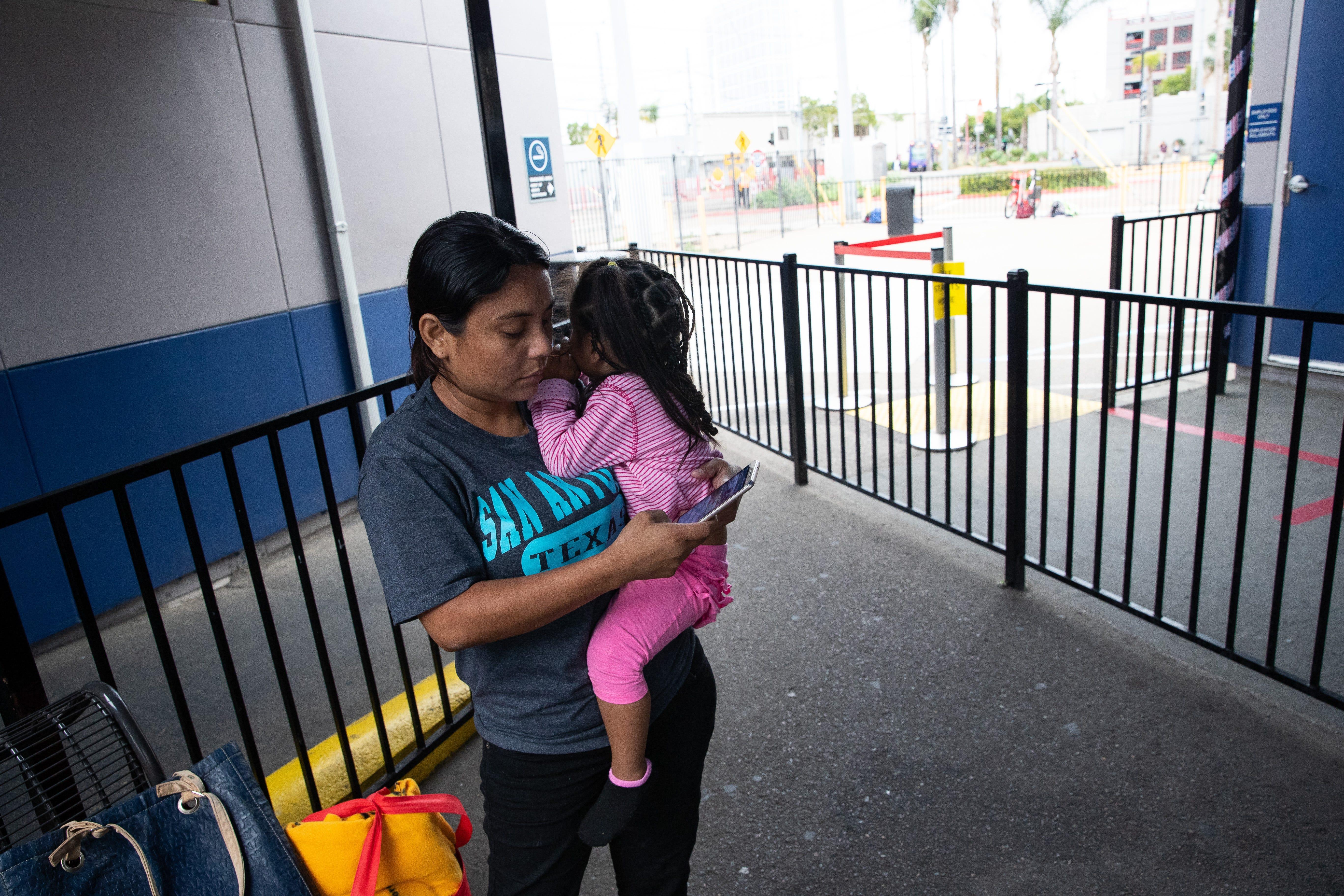 SAN DIEGO, Calif.  – Delmy López, 31, un migrante hondureña, le envía un mensaje de texto a su cuñado mientras carga en brazos a su hija de dos años, Perla, en la estación Greyhound al final de un viaje de dos días de San Antonio, Texas, a San Diego, el 29 de junio del 2019.