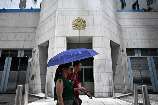 """Pedestrians walk past the British Consulate-General building in Hong Kong on August 20, 2019. - Britain's Foreign Office said on August 20, it was """"extremely concerned"""" by reports that a Hong Kong consulate employee had been detained by mainland Chinese authorities on his way back to the city."""