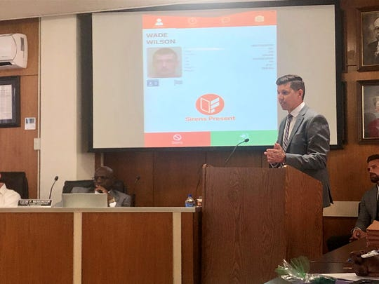 Ident Solutions representative McKay Johnson (right) shows Rapides Parish School Board members how its FedCheck software program works. The board will consider a motion to contract with the private company to place the program in Rapides schools.