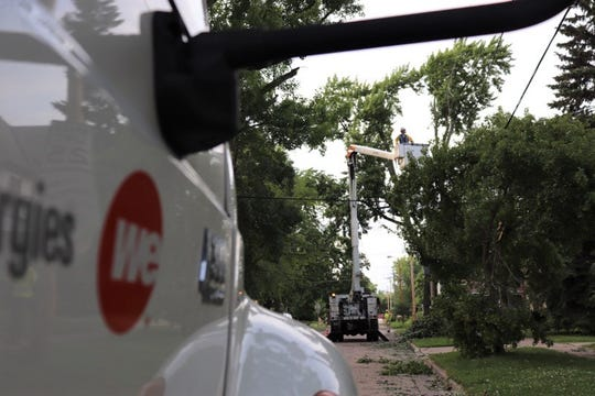Crews from We Energies work to restore power in Appleton on July 21 after damaging storms swept through the area.