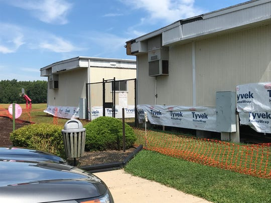 The Wall Township school board stopped repair work on two damaged and ant-filled trailers at Central Elementary School. Flexible fencing and caution tape now surrounds the buildings.